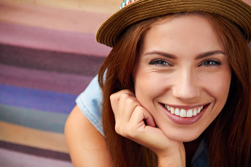 young woman in hat smiling
