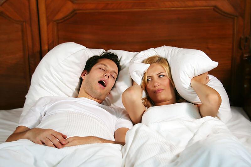 woman being kept awake by her husband's snoring