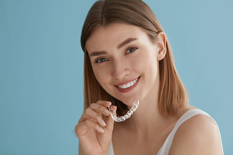 woman smiling and holding Invisalign aligners