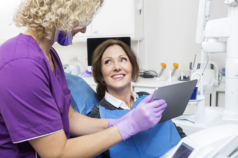 middle-aged female patient smiling during her dental exam